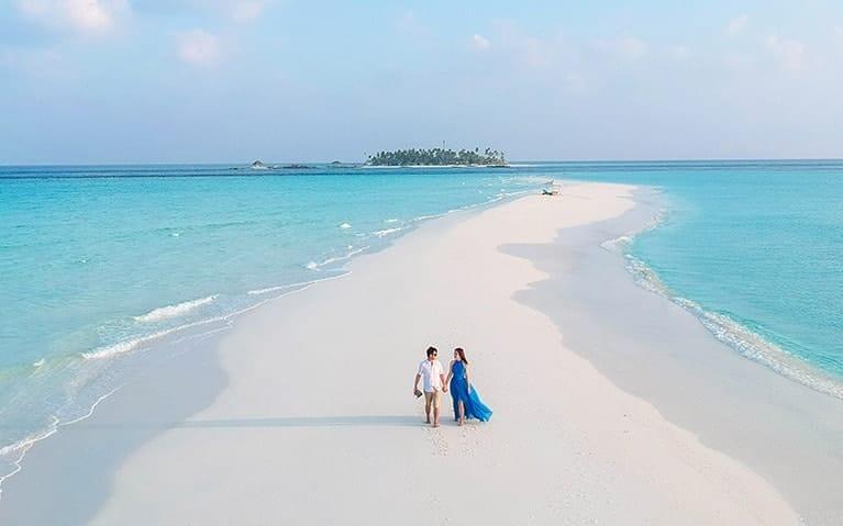 A couple enjoying a stroll on the beach