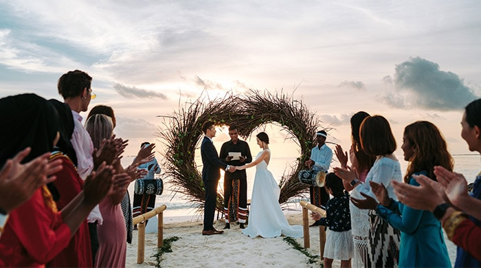 Couple taking vows at the wedding ceremony on the beach