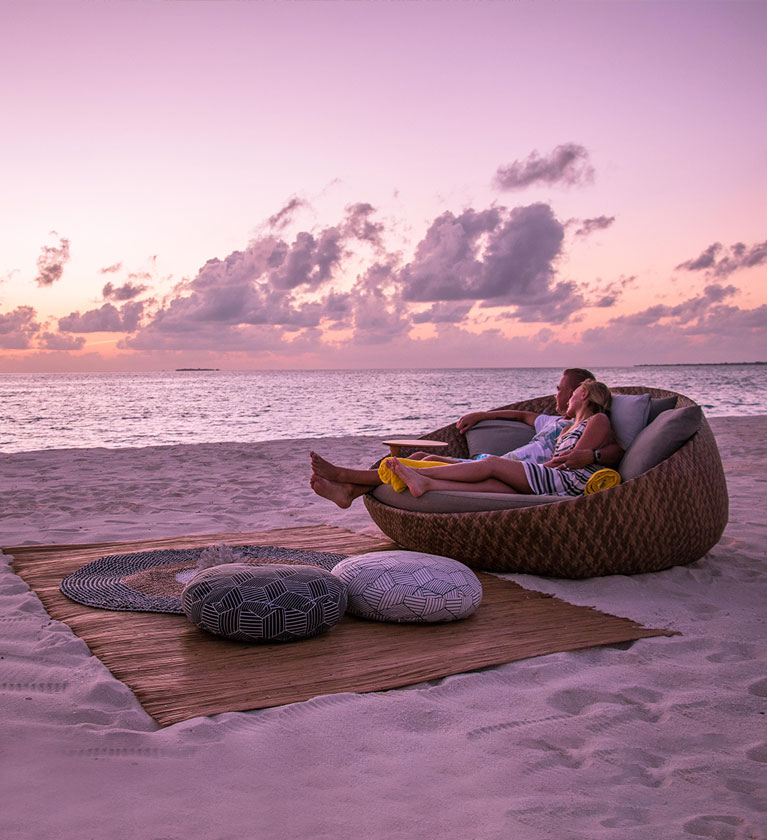A couple enjoying a night with under the stars with an ocean view