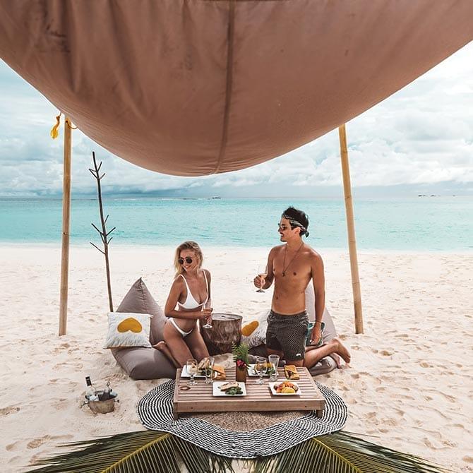 Two guests enjoying a private sandbank picnic
