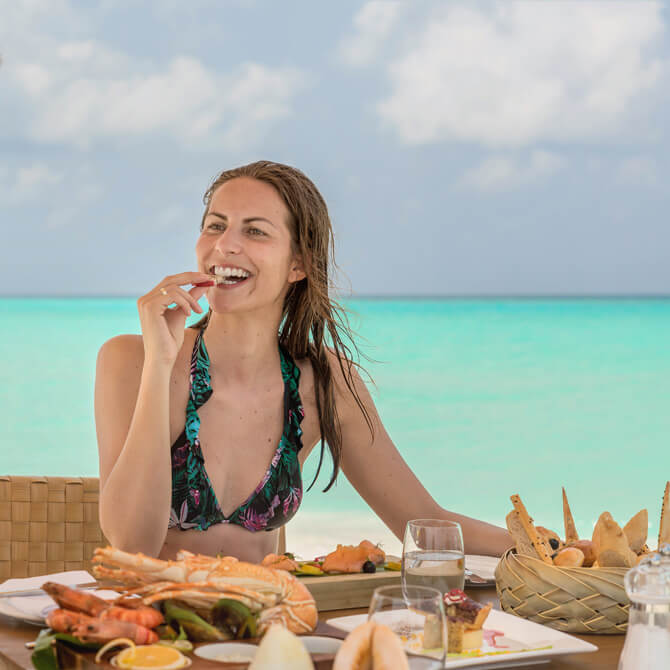 A guest enjoying seafood platter with a beautiful ocean view