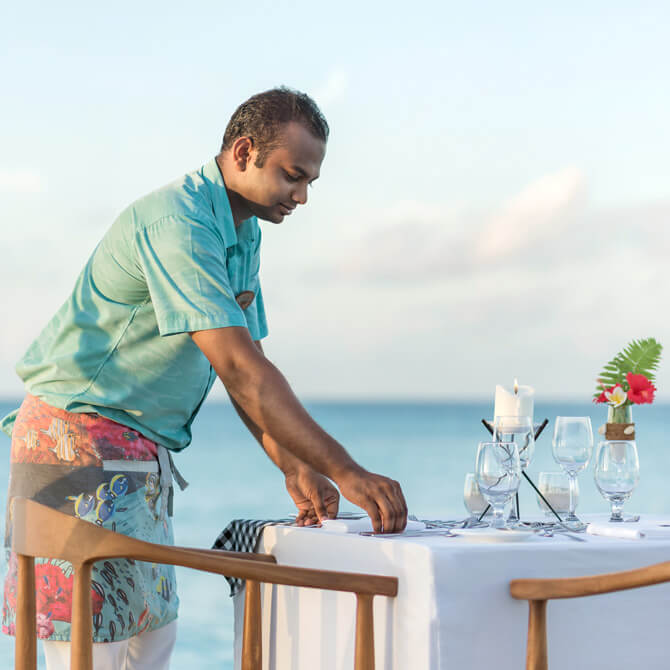 Staff at Fushifaru Maldives setting up a table