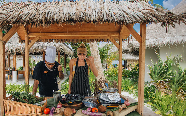 A guest tasting prepared Maldivian breakfast with a chef