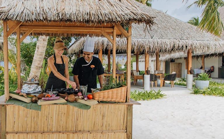 A guest enjoying preparing a Maldivian breakfast with a chef