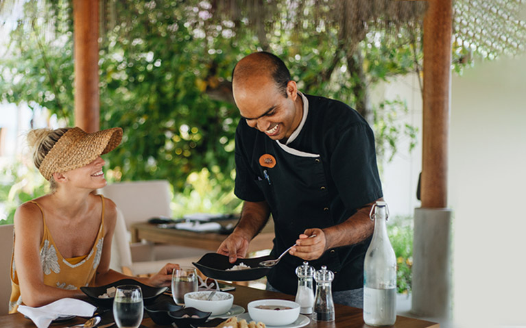 A chef serving a Maldivian breakfast for a guest