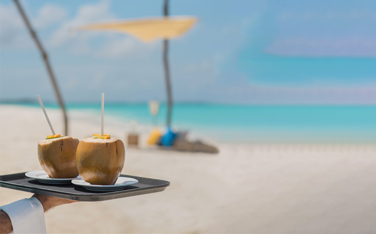 Two beverages served in coconuts for the guests enjoying private sandbank picnic