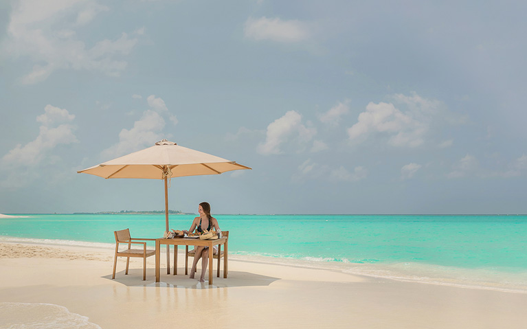 A guest enjoying the private sandbank picnic with a beautiful ocean view