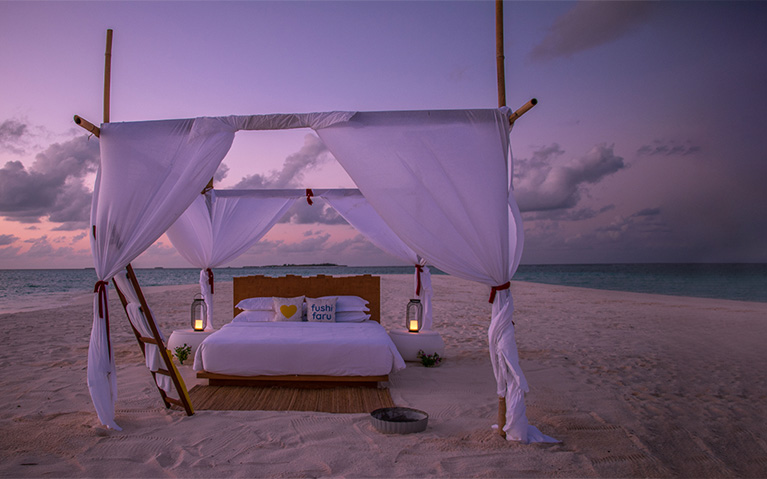A bed on white sand besides sparking waters of the Indian Ocean