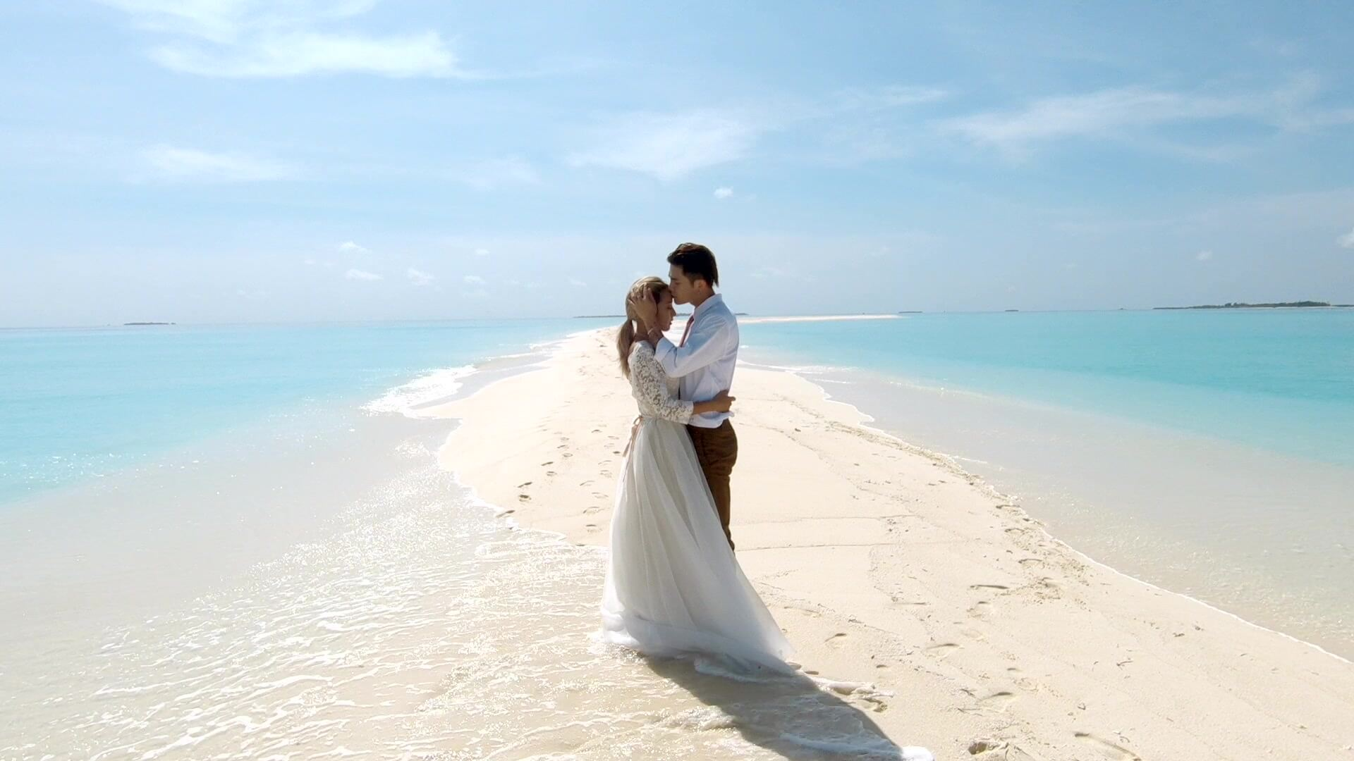 A romantic moment of a wedding couple on sandbank Maldives